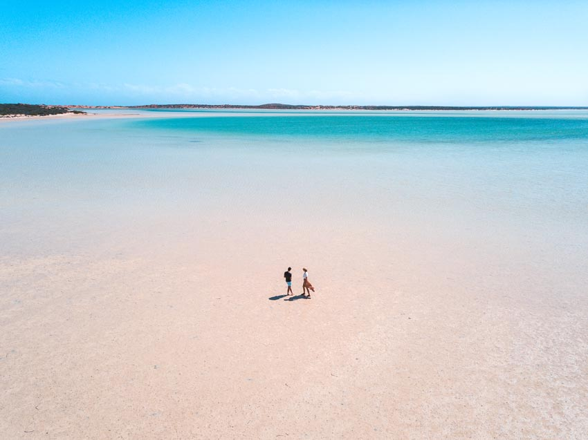 2 people standing in the blue water with a view on blue lagoon in Shark bay