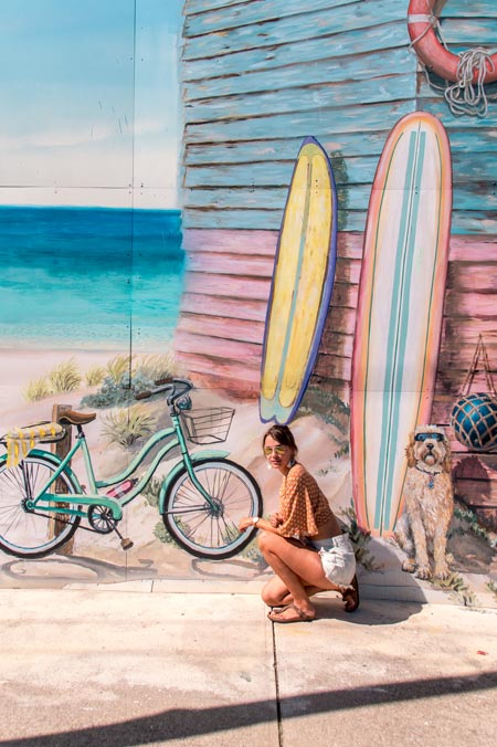 a girl posing in front of the painted wall with bicycle, a dog and two surfboards in Fremantle a good starting point for a trip from Perth to Esperance