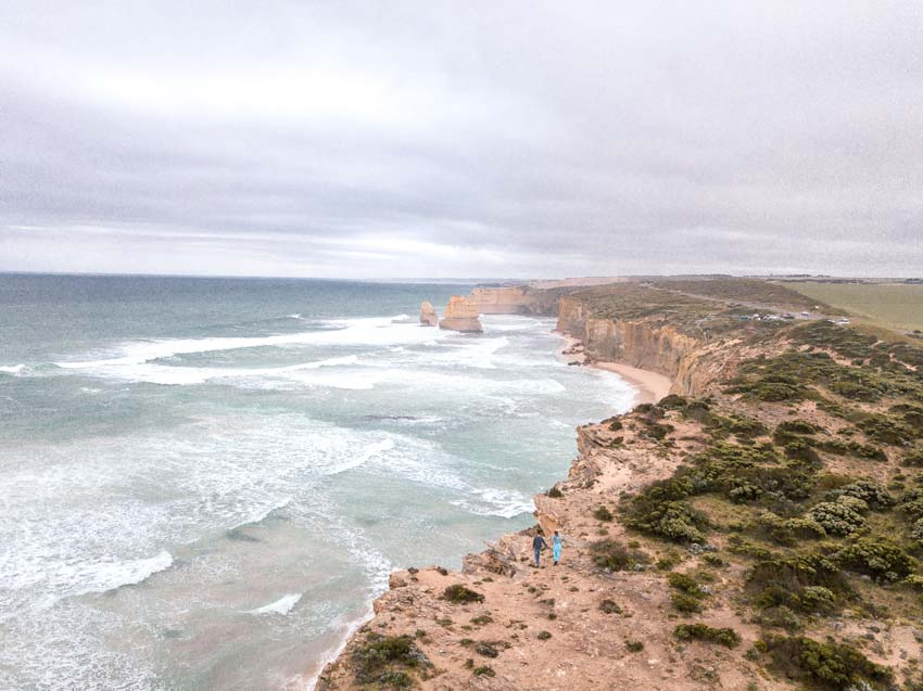 and arial shot on two people standing with view on Twelve Apostles