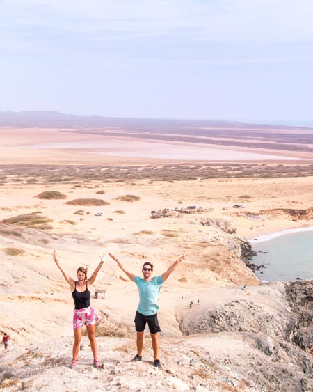 two people having hands in the air with desert of Guajira and ocean in the background.