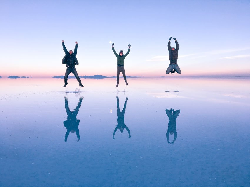 three people jumping in the air at the sunset which is a must do in salt flats in Bolivia