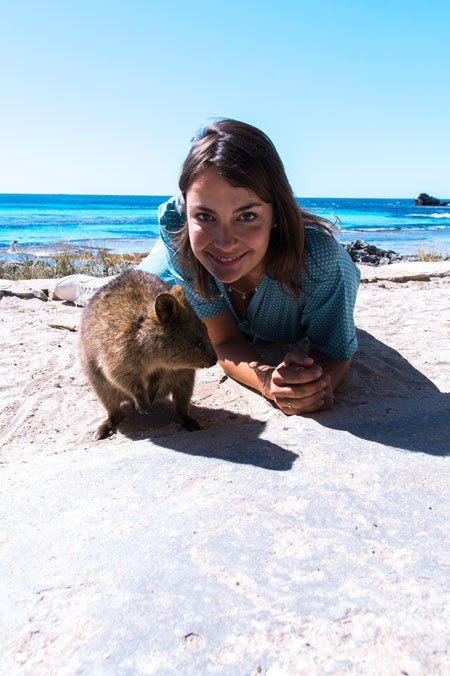 a woman laying on the ground and trying to take a quokka selfie