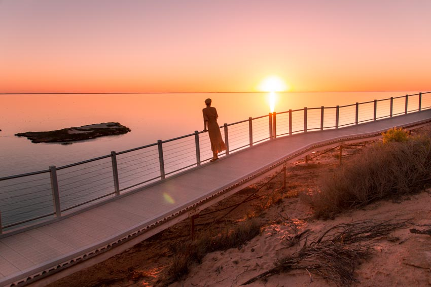 a girl standing on the boardwalk with pink and orange sunset colors which is the most beautiful things to do in Shark Bay.