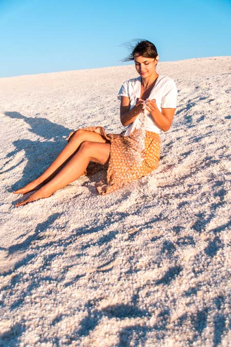 woman sitting on the Shell beach and throwing shells in the air