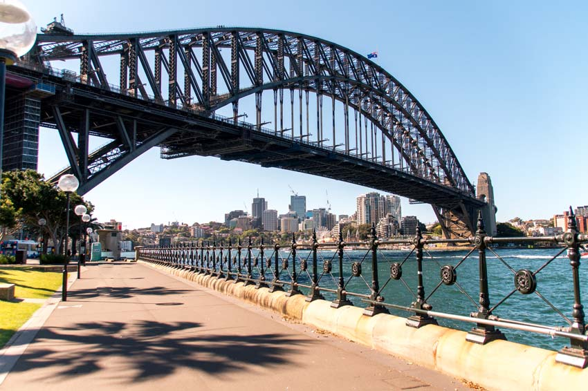 the view on the Harbour bridge in Sydney with blue water and skyline in the background.
