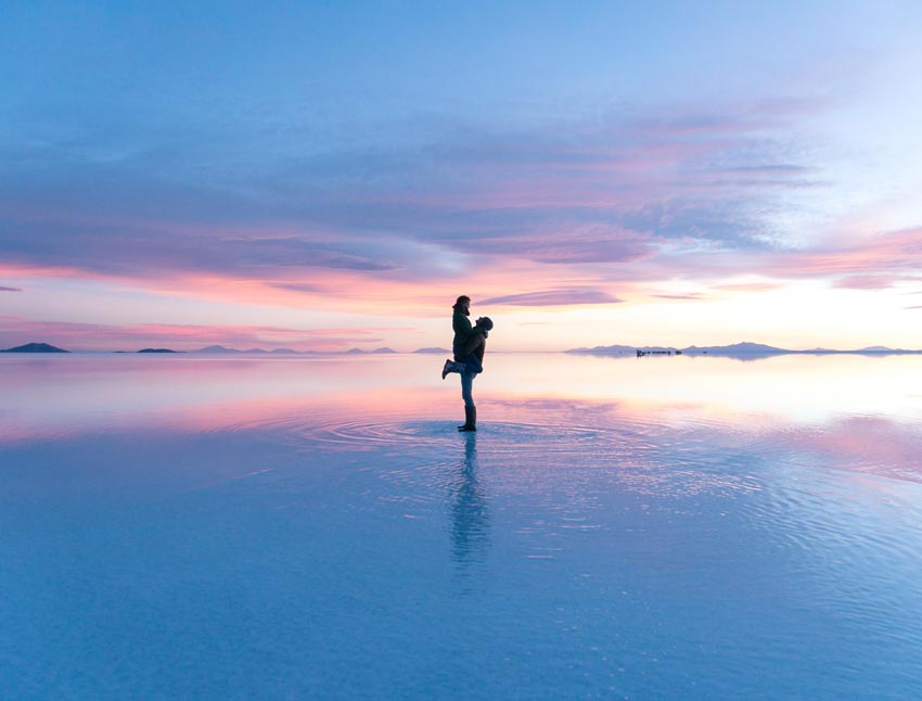 a men holding a woman in the air surrounded by pinky sunset colours during sunset in salt flats in Bolivia