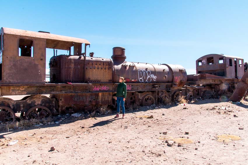 a girl standing in front of a rusty train