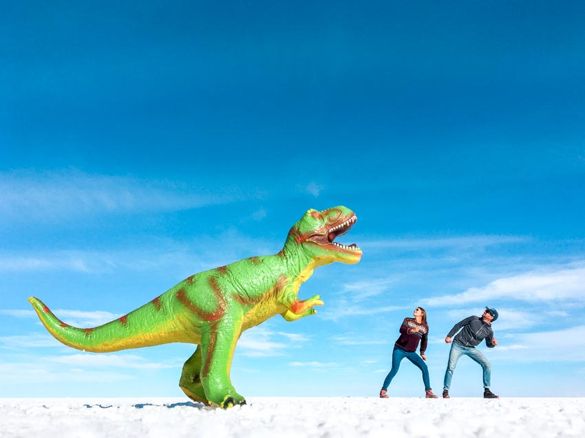two people running from a dinosaurs during a day trip in Salar de Uyuni
