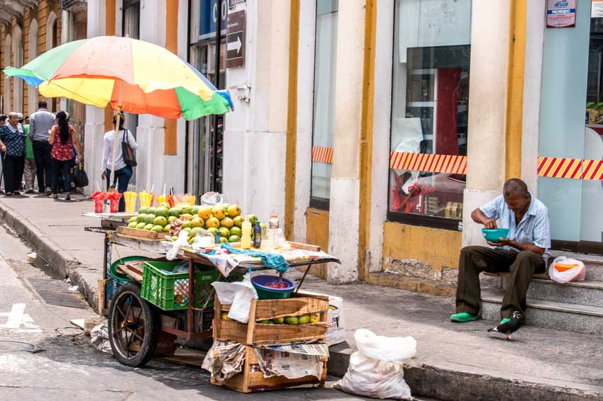 colourful beach umbrella with a fruit stand and a men eating from a bowl