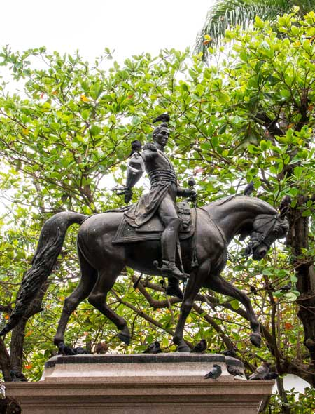 statues of a men and a horse in front of the green tree