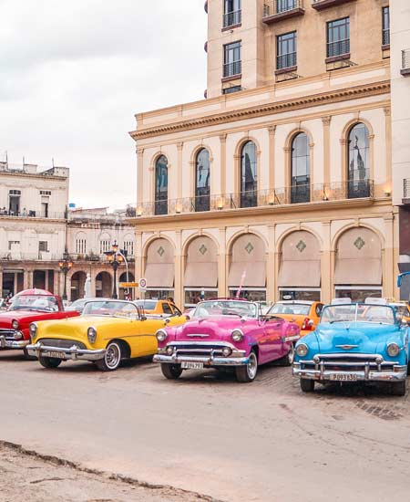 pink, yellow, blue and red cuban cars ready to take you for a ride during your 10 days in Cuba
