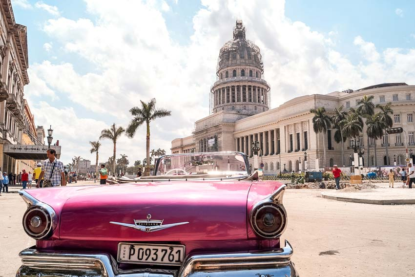 a pink Chevrolet car with the view on the building in Parque Central, Havana