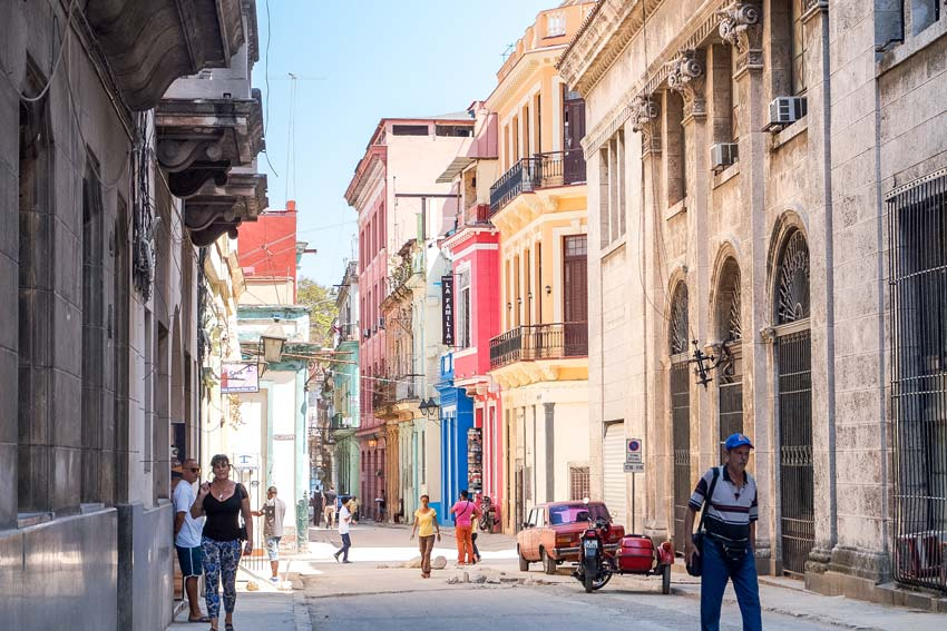 locals walking in the colourful streets of Havana which you need to see during 10 days in Cuba.