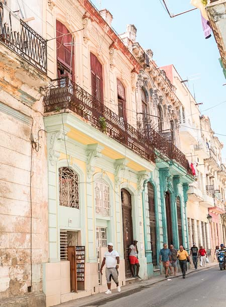 locals walking in the colourful streets in Havana Vieja