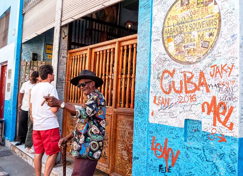 Local in Havana is offering cigars to tourists