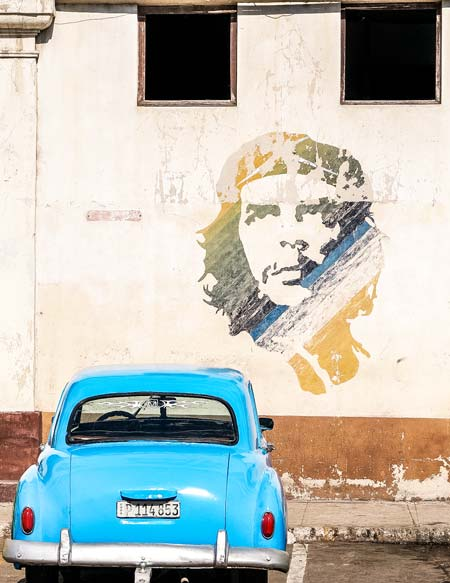 blue old car and the portrait of Che Guevara in Havana