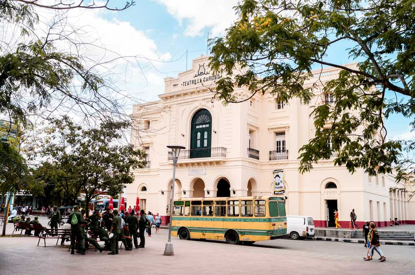 view on white building, yellow bus and locals in uniforms