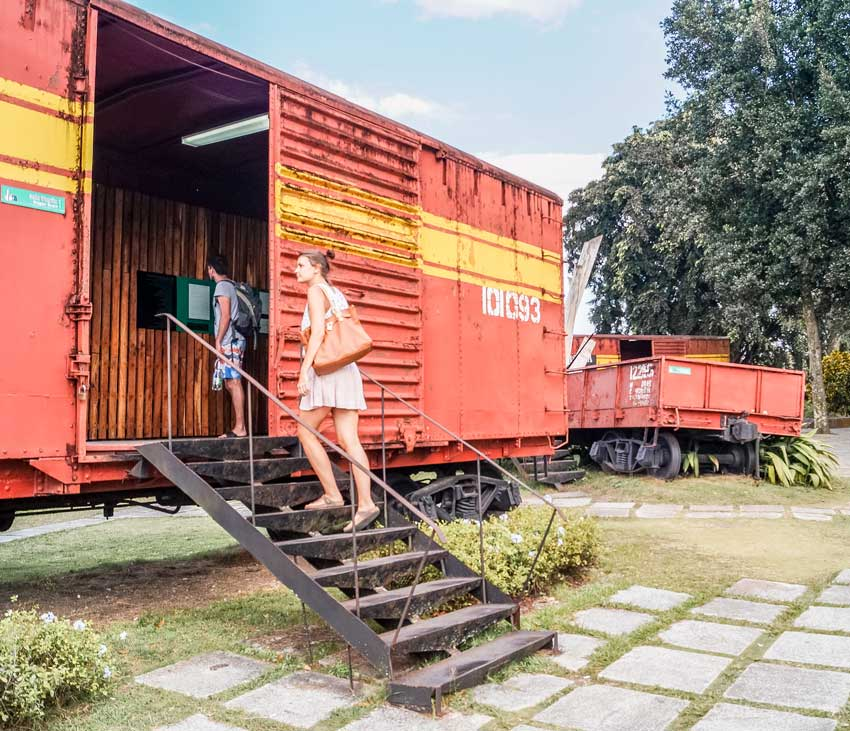 woman in a pink dress entering a red train in Tren Blindado Monument which is the best things to do in Santa Clara