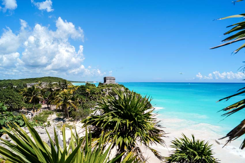a view in Castello in Tulum, blue water and green palm trees,  which needs to be in your travel guide