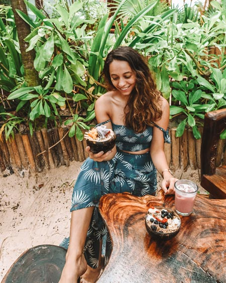 a woman in a green dress sitting at the wooden table and holding an açai bowl in Tulum