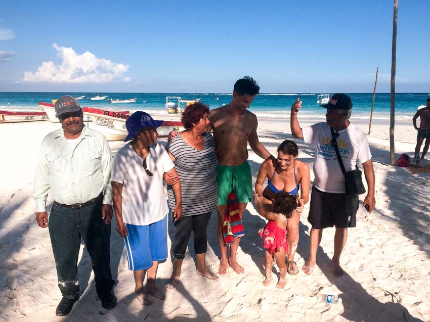six people and a little baby taking a photo on Playa Paraiso