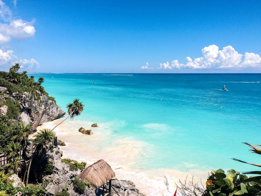 a view on Tulum ruins with blue water, palm trees which needs to be in your itinerary