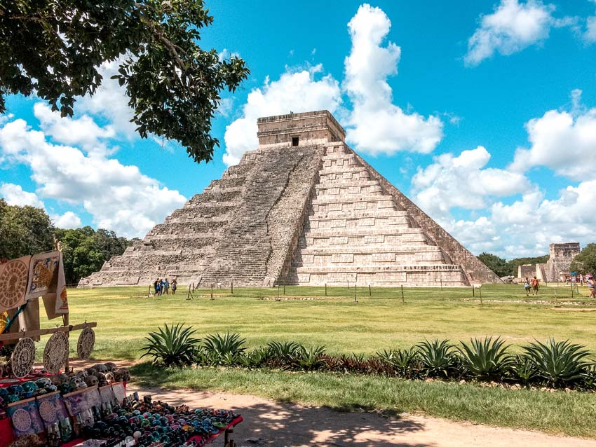 a view on the pyramid of Chitzen Itza, blue skies and green grass