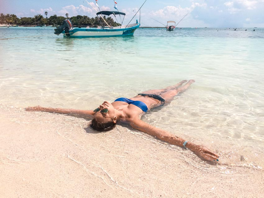 a woman laying in the blue water in Akumal which needs to be in Tulum itinerary.