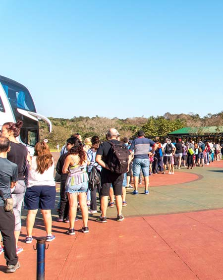 Many people standing in the line for the tickets to Iguazu