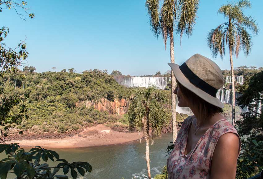 A girl with a hat standing in front of the Iguazu waterfalls and green palm trees