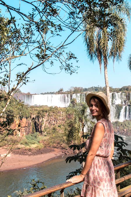 a girl standing in front of the Iguazu falls in Argentina