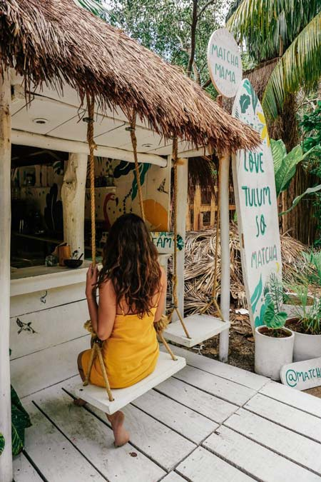 a girl in a yellow dress sitting on the swing in Matcha coffee in Tulum