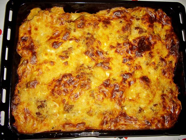 pan full of fried cheese, vegetables and minced meat