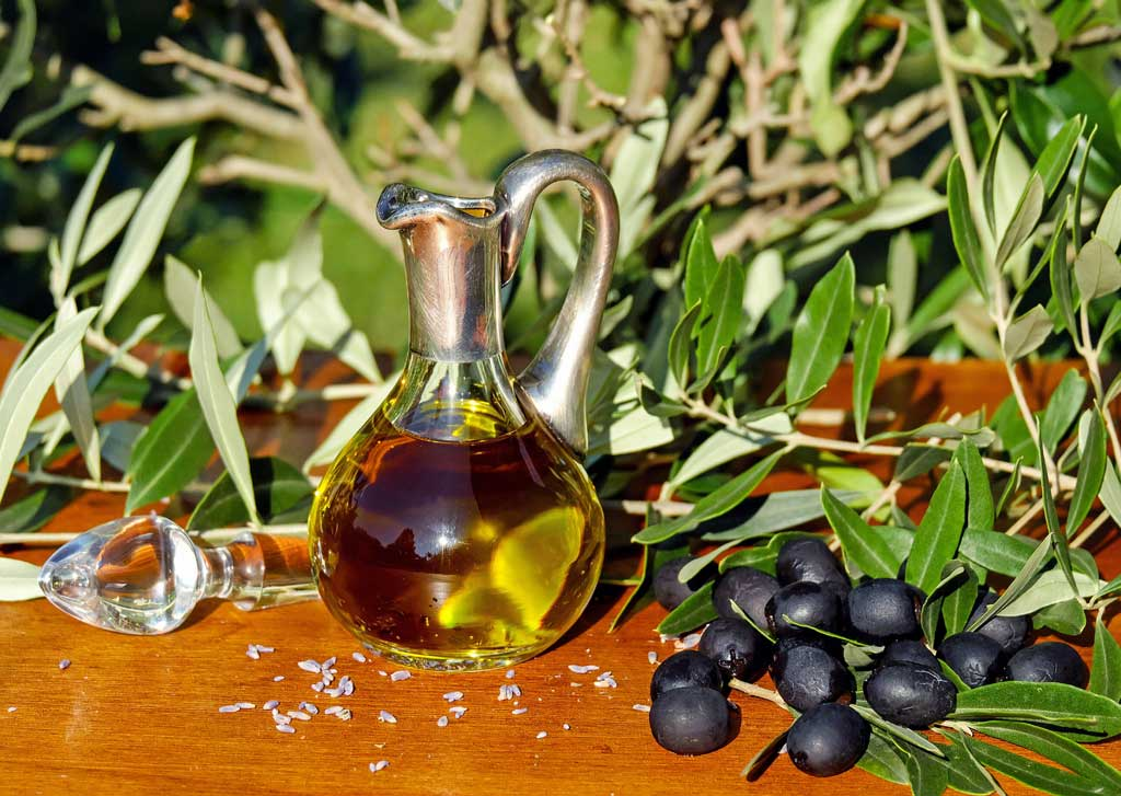 photo of a bottle of olive oil and black olives