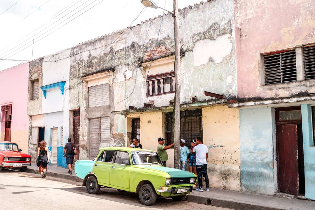 green car, locals talking in front of the destroyed building in Santa Clara in Cuba