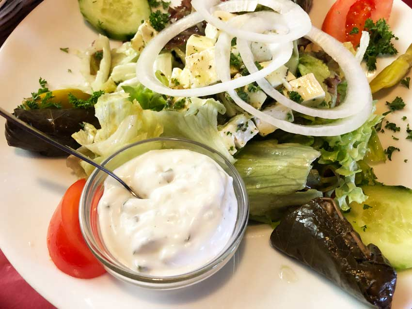 white sauce Tzatziki with green salad, onion, tomatoes, a must traditional greek meal