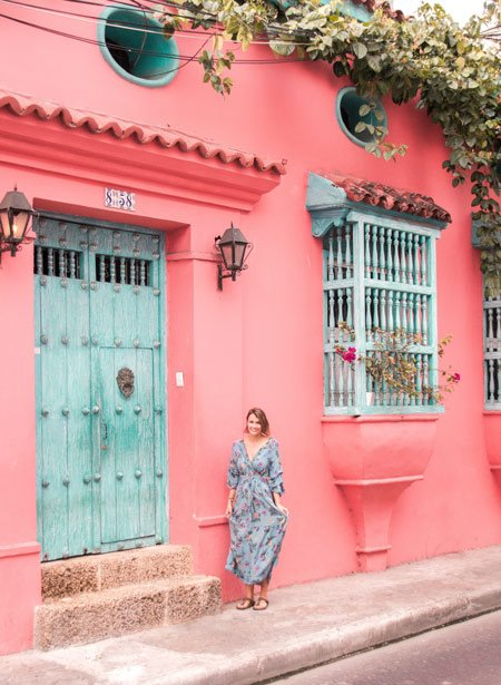 woman in a blue dress standing in front of the pink wall and blue door in Cartagena