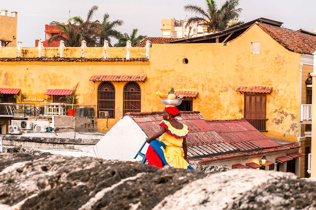dreamy bucket list place called Cartagena, woman in a yellow dress walking in front of the orange building