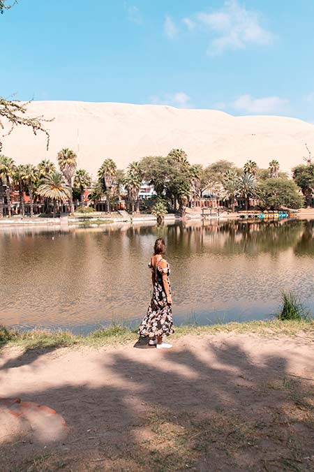 a woman standing in front of the Laguna Huacachina, palm trees and white sand dunes