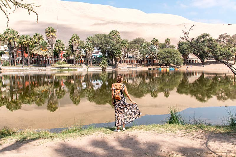 a woman standing in front of the green water, holding her dress, tree reflection and Huacachina sand dunes in Peru
