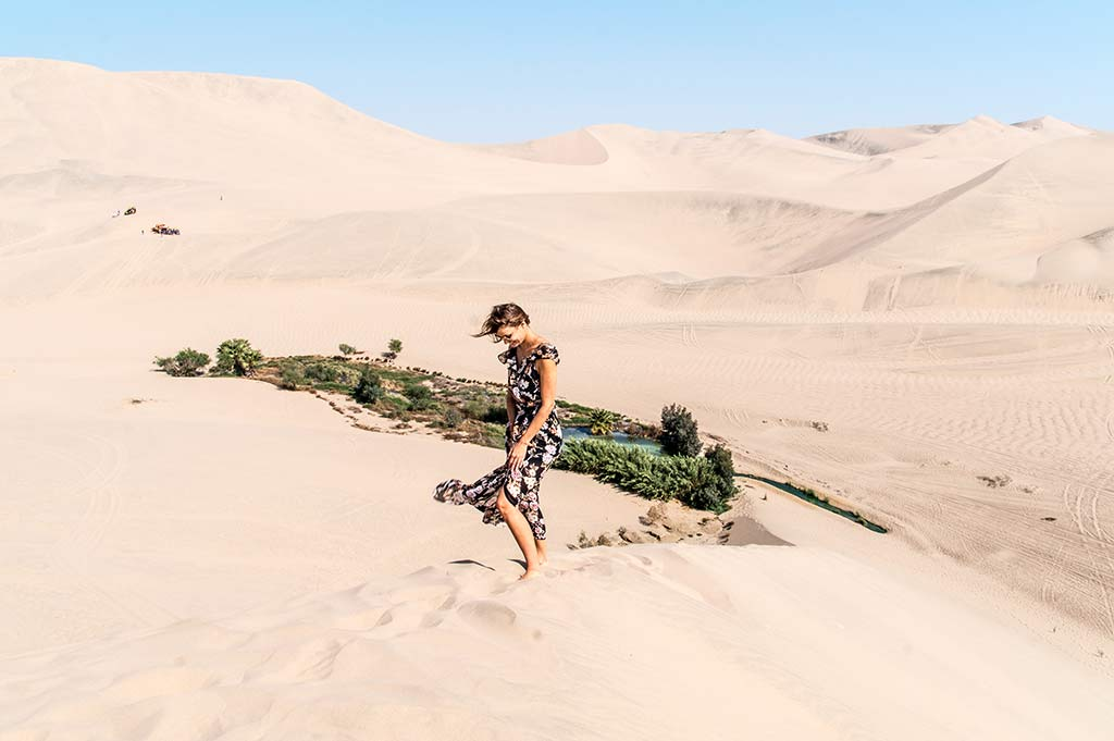 a woman standing on the sand hill with green oasis in the background