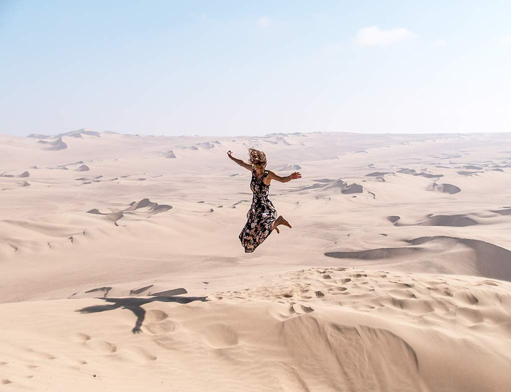 a woman jumping in the air in sand dunes in Huacachina
