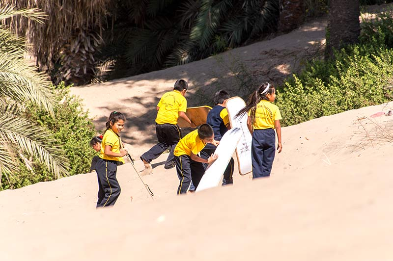 six school kids in yellow shirts holding white sand boards and walking on white sand
