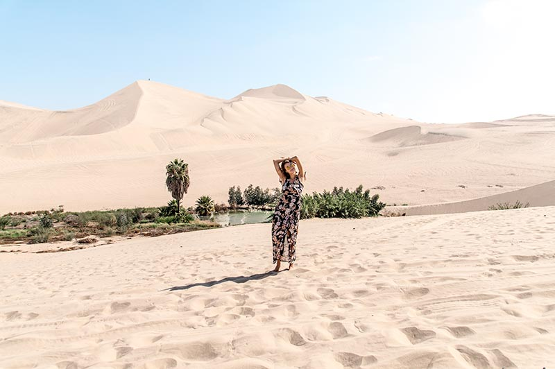 woman in a flowery dress walking on the sand with green oasis at the background in Huacachina in Peru