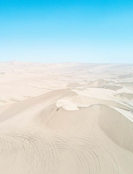 an arial shot on white sand dunes and blue sky