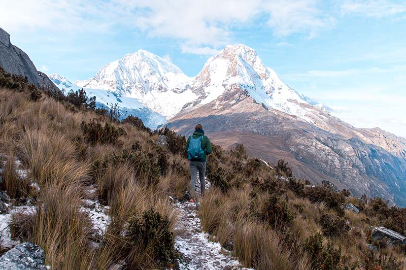 snowy mountains of Huascaran, and woman with blue backpack walking among green bush