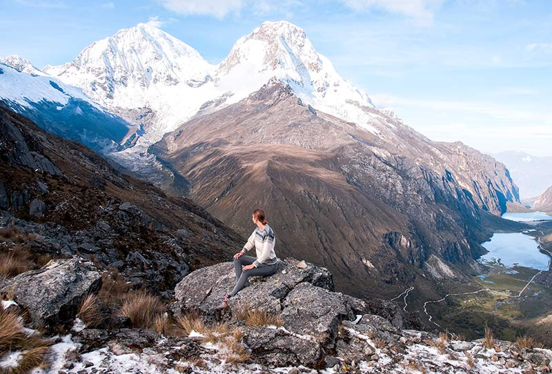 a woman sitting on the rock in front of the, Huarascan, snowy mountains and lakes