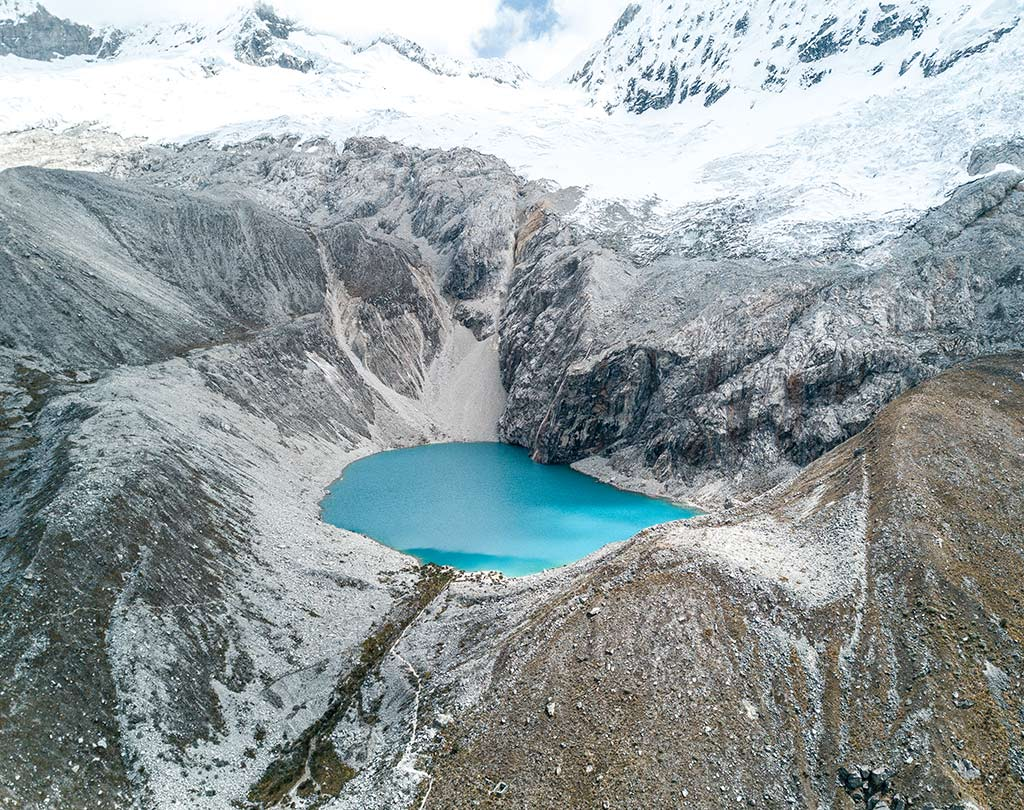 a view on Laguna 69 in Peru, turquoise water and white mountains near Huaraz