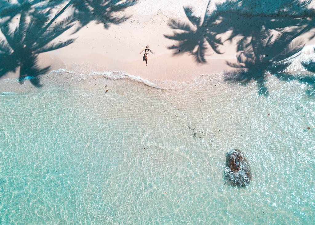 arial shot on the palm trees, woman laying on the beach and blue water on Koh Kood, Thailand