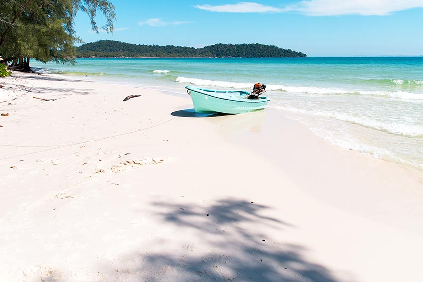 blue boat on white sand beach with blue water and green hills